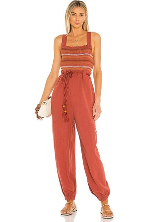 Free People Sienna Smocked Jumpsuit in - Brick. Size L (also in M, S, XS).