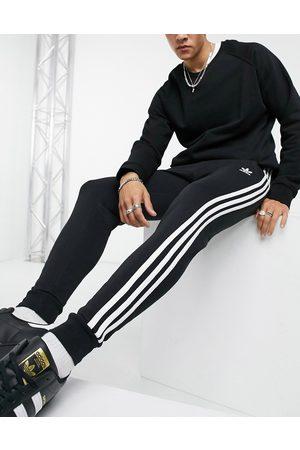 adidas Adicolor three stripe skinny joggers in black