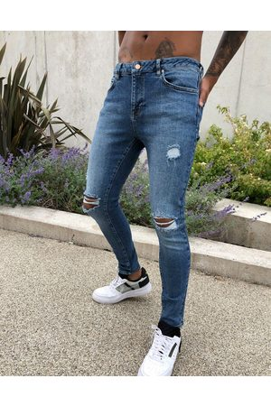 ASOS Spray on'vintage look' jeans with power stretch in dark wash blue with abrasions