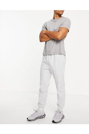 Reebok Herren Lange Hosen - Training fleece joggers with logo in grey