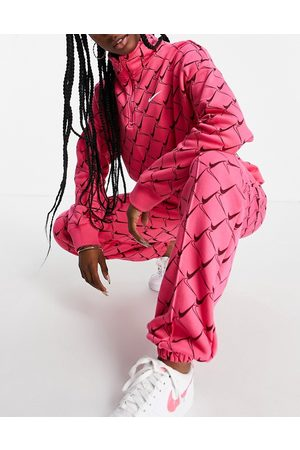 Nike Oversized joggers in watermelon pink with all over swoosh print